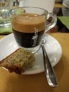 An orzo espresso in a glass espresso cup, on a ceramic plate with a spook and a small piece of a poppy seed pastry.