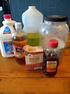A photo of cake ingredients, including (left to right) almond milk, apple cider vinegar, baking soda, oil, honey, and flour.