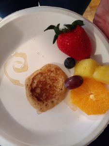 A white plate with a small pancake, a blueberry, a grape, a piece of pineapple, a piece or orange, a strawberry, and a swirl of maple syrup in the shape of the Debian logo.