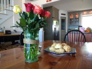 A table, containing a glass jar full of multi-colored roses, and a plate of biscuits.