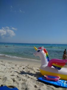 A photo of a beach in Greece, with bleach and tourquoise water and well trodden sand. In the forground is an inflatable uniforn with a rainbow mane.