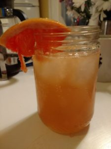 An ancho paloma, in a peanut butter jar, with a grapefruit wedge.